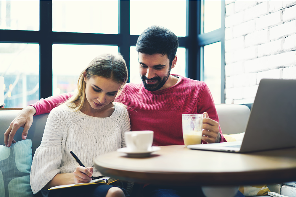 Couple sitting down, drinking coffee and making list