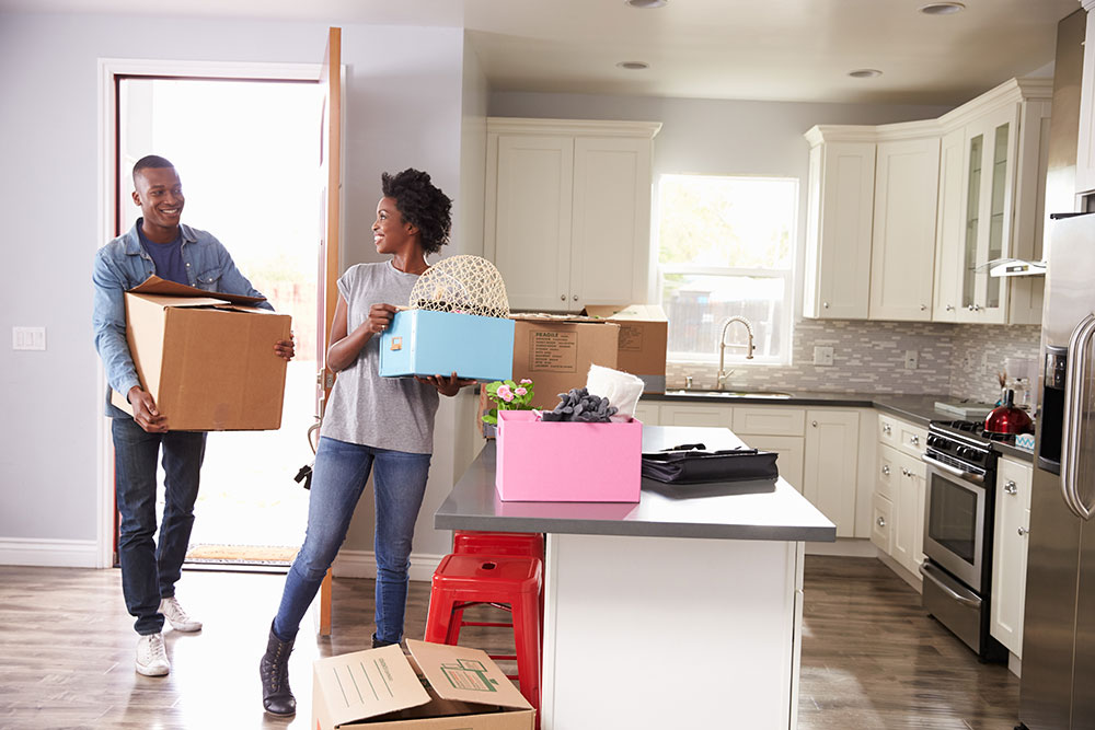 Couple moving into new apartment in kitchen holding boxes