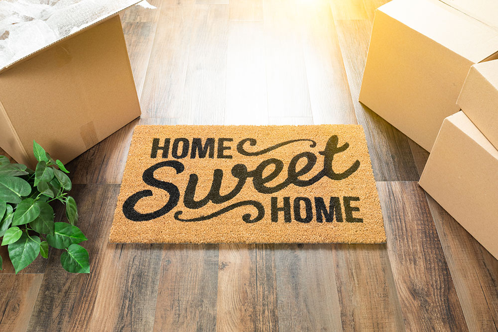 Door mat that says home sweet home laying on wood floor