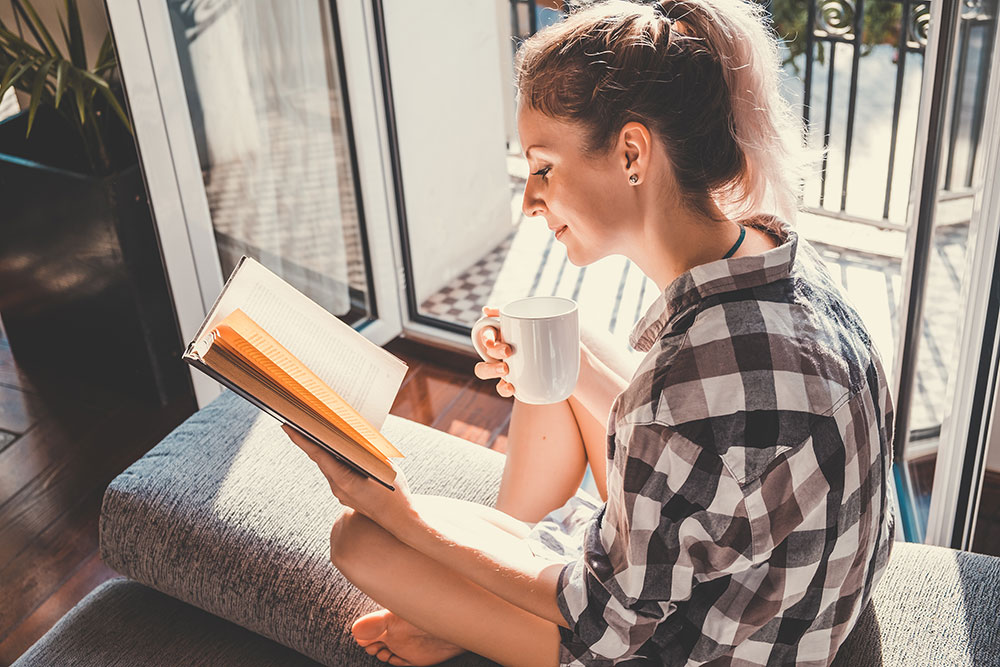 Woman sitting on balcony drinking coffee and reading a book