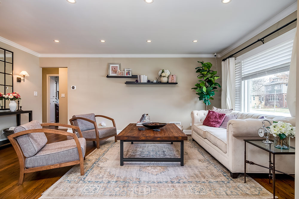 Spacious living room with two chairs, sofa, coffee table, and large area rug