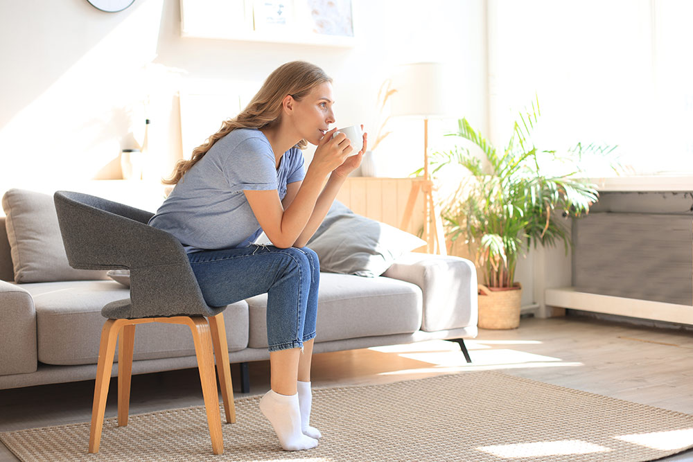 Woman sitting in chair drinking coffee in apartment living room